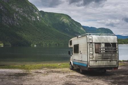 Wohnmobil steht in der Natur an einem See